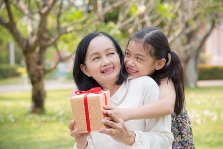 Foto de Asian granddaughter giving birthday gift for granddaughter in the garden.Happy Asian family conception. - Imagen libre de derechos