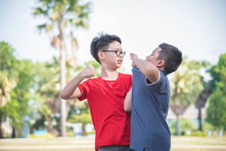 Photo pour Asian schoolboy getting bullied ,Children fighting with classmate in school park. Bullying and violence in school concept. - image libre de droit