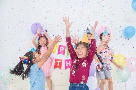 Foto de Happy Asian Girl Enjoy Throwing Colorful Confetti with Friends in Birthday Party - Imagen libre de derechos