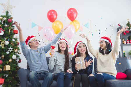 Photo pour Three beautiful asian girls and a man celebrating Christmas or the New Year's Eve party - image libre de droit