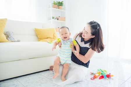 Photo pour Little asian child smiles happily while playing with mother in living room - image libre de droit