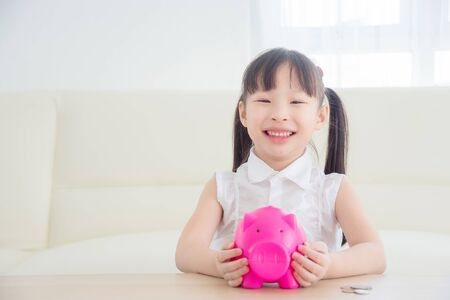 Foto de Little asian girl holding pink piggy bank and smiles,Money saving concept. - Imagen libre de derechos