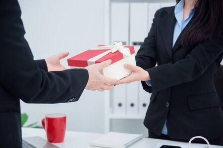 Foto de Hands of businesswoman giving christmas gift to her boss in office. - Imagen libre de derechos