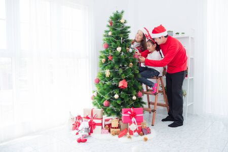 Photo pour Happy asian family decorating christmas tree together at home. - image libre de droit