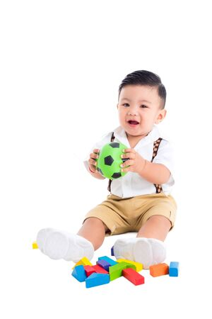 Photo pour Little asian male toddler sitting on the floor and holding ball and smiles over white background - image libre de droit