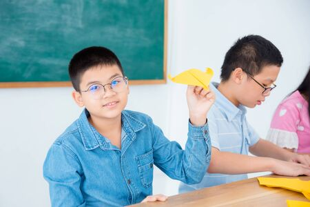 Photo pour Young asian boy playing paper airplane in classroom. - image libre de droit