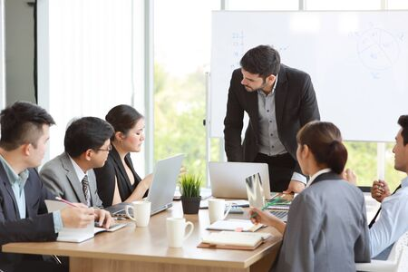 Photo pour caucasian lecturer giving public presentation with company business graph result on white board in meeting room and multiethnic business people are paying attention (training or seminar concept) - image libre de droit