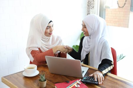 Photo pour new generation businesswoman muslim people shaking hands after finished business deal in coffee shop with computer and coffee cup on wood desk - image libre de droit