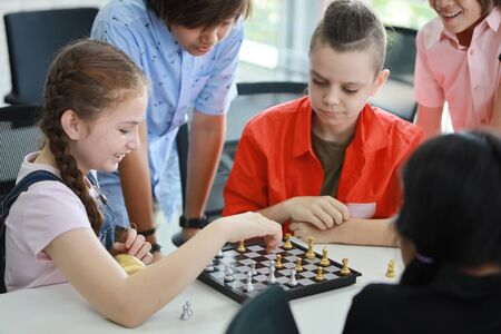 Photo pour cute and smart kids playing chess in class (education concept) - image libre de droit