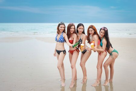 Foto de group of happy and sexy asian friends who wearing bikini and swiming suit. they drinking and cheering with alcohol and soft drink bottle on sandy beach party. young people having fun and happiness face. - Imagen libre de derechos