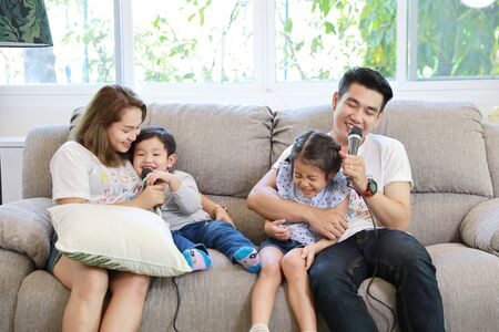 Foto de Happy Asian family, father, mother daughter and son singing karaoke on the sofa in the living room with happy smiling face (relaxation and technology concept) - Imagen libre de derechos