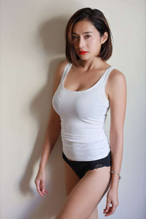 Photo for full length young adult asian woman, red lip and short hair in white dress with beauty face and looking at camera on white wall - Royalty Free Image