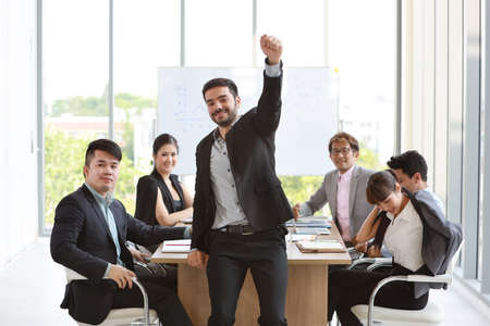 Foto de Multiethnic business people discussing company profit or project result in meeting room then they showing thumb up meaning of their job is success with smiling and happy faces - Imagen libre de derechos