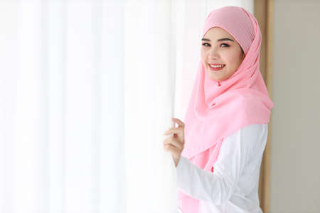Photo pour Side view beautiful asian muslim woman wearing white sleepwear, standing at window after getting up in the morning at sunrise. Cute young girl with pink hijab relaxing while looking at camera - image libre de droit