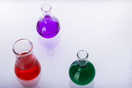 Laboratory glassware with liquids of different colors on white background.
