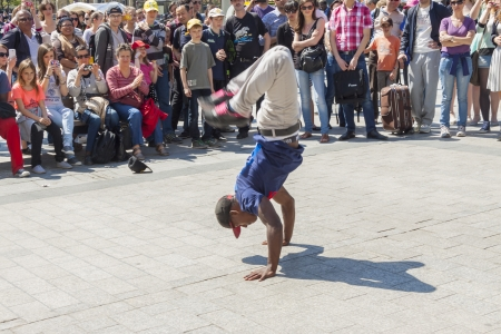 PARIS, FRANCE -  APRIL 25 B-boy doing some breakdance moves in front a street crowd, at Arch of Triumph on april 25, 2013 in Paris  Its popular form of earnings in big cities