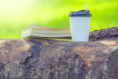 Paper cup of coffee and book on branch in summer sunlight park