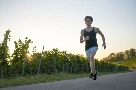 Photo for Young man in white shorts and tanktop dancing next to vineyards - Royalty Free Image