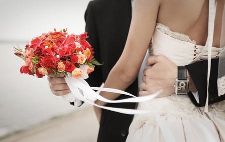 groom with bouquet embracing bride