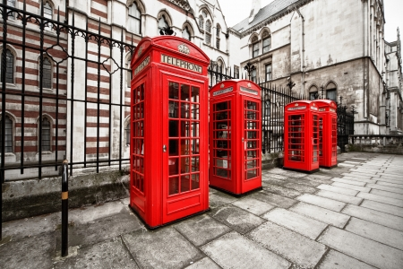 horizontal shot of four red phone boxes on London