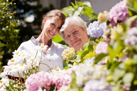 geriatric nurse with senior woman in the garden