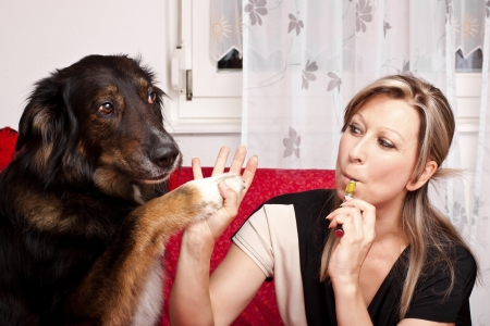 Blonde cute woman give dog high Five and evaporated electric cigarette