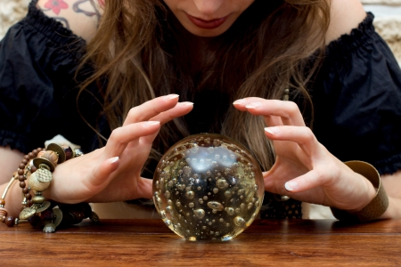 Young fortune teller indicated something in a ball