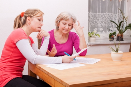 Two women pondering in living room over documents