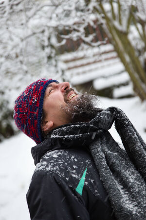 a laughing man is outside in the snow