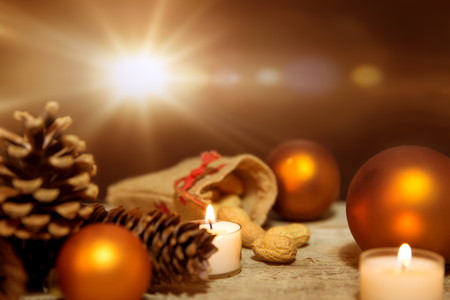 Festive christmas decoration in orange and white, lightning candles, fir cones, christmas balls and wooden background