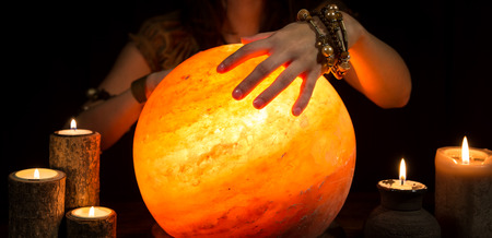 Photo pour Hands of a female fortune teller, a shining crystal ball and candles - image libre de droit