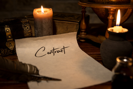 a parchment paper with a quill and ink, candles and medieval decoration, concept contract