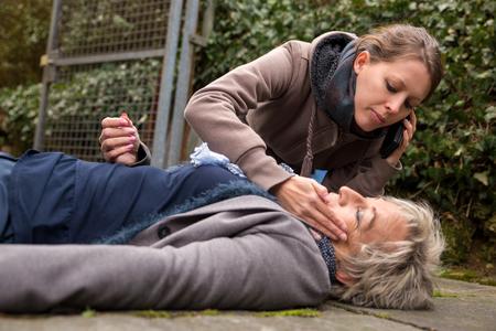 Photo pour senior adult had an collapse, a young woman do first aid - image libre de droit