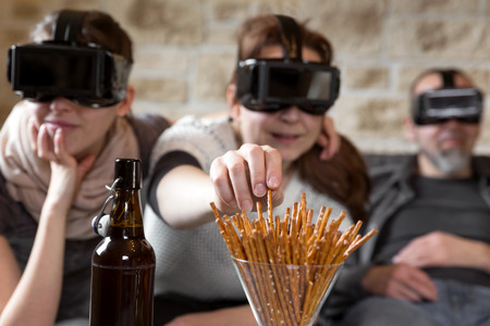 Photo pour three people with virtual reality glasses and snacks, having fun - image libre de droit