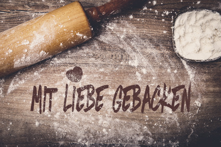 Dough roll and flour on wooden table, german text mit liebe gebacken which means baked with love