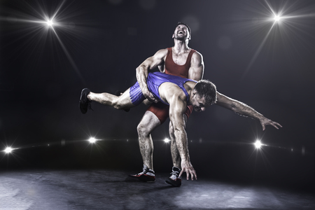 Wrestler throwing against the lights on background
