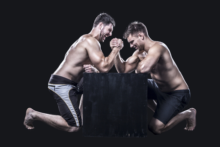 Photo pour Two armwrestlers, have an arm wrestling match on a black box shirtless - image libre de droit
