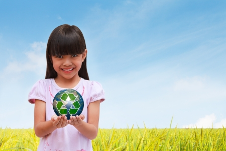 Smiling little girl holding earth with recycle symbol