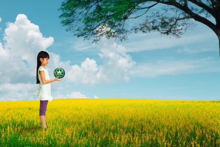 Little girl holding earth with recycle symbol at flower field, Elements of this image furnished by NASA