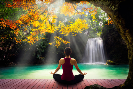Young woman in yoga pose sitting near watefall Rear view