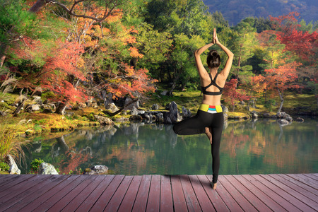 Young woman training yoga outdoor in autumn or fall park