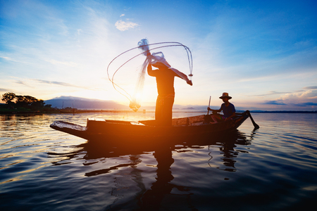Photo pour Silhouette of fishermen using nets to catch fish at the lake in the morning - image libre de droit