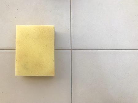 Foto de yellow sponge for wash cleaning on ceramic tile wall background. - Imagen libre de derechos