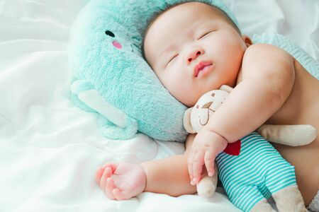 Photo for Portrait of a newborn Asian baby on the bed, A child resting on a bed sleeping - Royalty Free Image