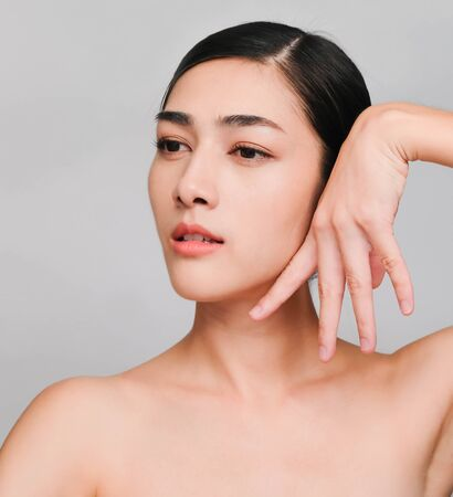 Photo pour Beautiful young brunette posing,Youthful bright skin pretty Asian woman with clean and bright skin, Cosmetic Beauty Concept,hands touch on the cheek, smiling face isolated on grey background - image libre de droit