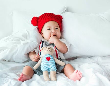 Photo for Portrait of a newborn Asian baby boy, Charming child 5 month old wore a suit and a red wool hat sitting in bedroom sucking his finger,fat baby cute and smilingly with a doll,soft selective focus - Royalty Free Image
