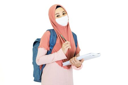 Photo for beautiful young muslim asian woman with traditional dress wearing medical face mask  to go to school Under the outbreak of the virus isolated on white background,health care concept - Royalty Free Image
