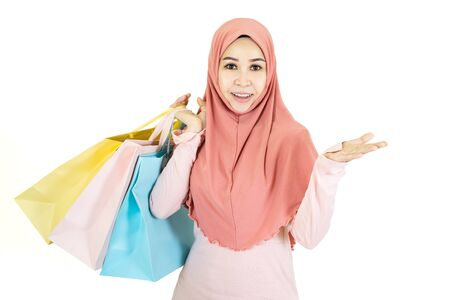 Photo pour Happy beautiful young muslim asian woman with traditional dress holding color shopping bag isolated on white background - image libre de droit
