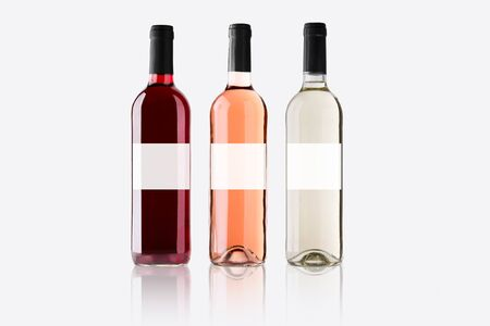 Bottles of red, white and pink wine on light background