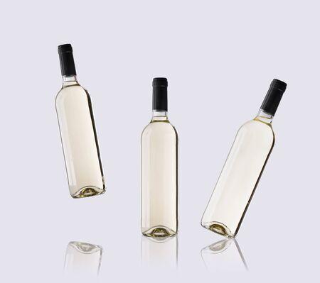 white wine bottles floating on light background